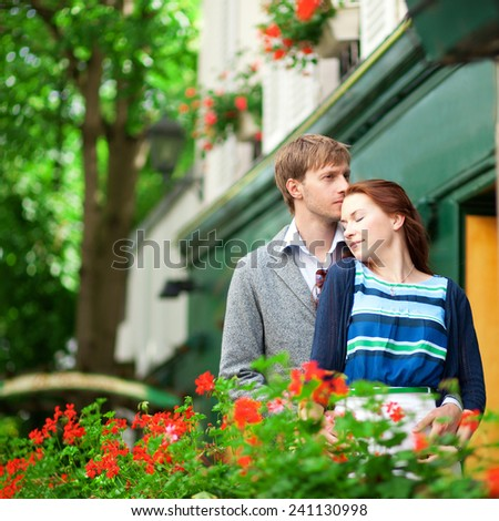 Man and woman together on balconyof their house or hotel with blossoming geranium and nice view
