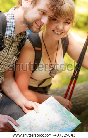 Man and woman tourists backpackers reading map on forest trip while resting. Couple hikers searching looking for direction guide. Backpacking summer vacation adventure..