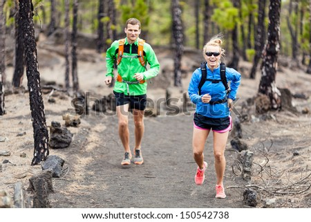 Man and woman trail running on volcanic trail in mountains. Young couple runners in forest  on beautiful island La Palma, Canary Islands. - stock photo