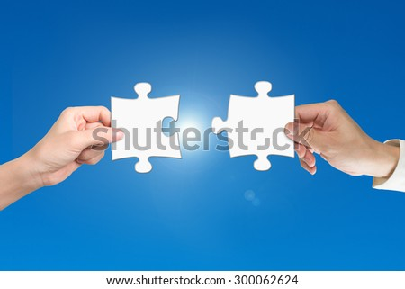 Man and woman two hands assembling jigsaw puzzle pieces, with blue background. Teamwork concept.