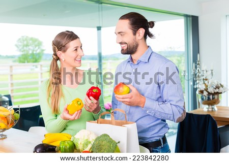 Man and woman unpacking fruits and vegetables out of grocery shopping bag in home kitchen - stock photo