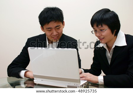 Man and woman use laptop together.