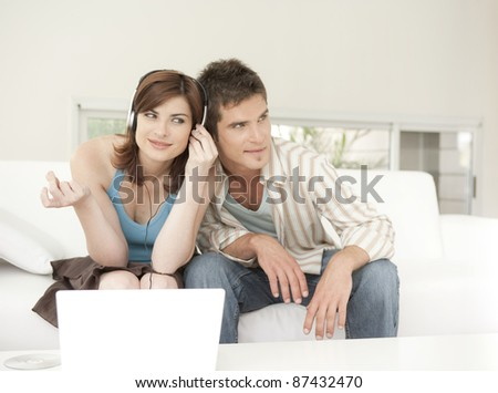 Man and woman using a laptop and listening to headphones at home.