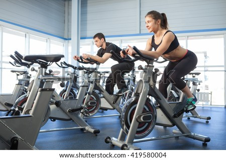 Man and woman using cycling exercise bikes at the gym - stock photo