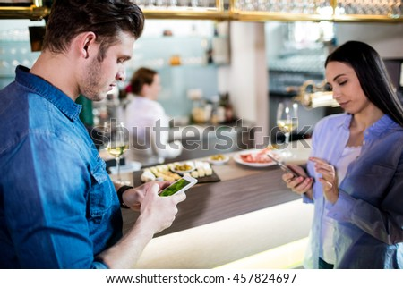 Man and woman using mobile phone while standing by bar counter