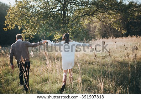 man and woman walk at sunset on the grass in a forest glade - stock photo
