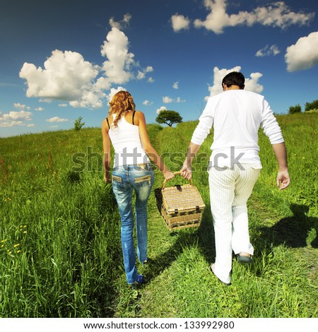 man and woman walk on picnic in green grass - stock photo