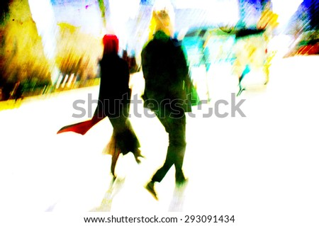 Man and woman walking along city sidewalk, passing a bus shelter.  Her coat flutters in the wind.  Their silhouettes blur with motion. - stock photo