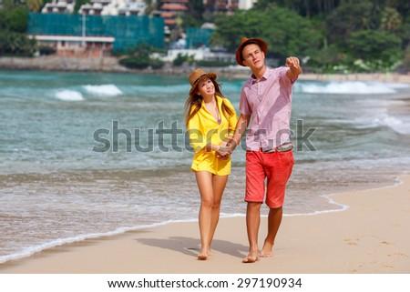 man and woman walking along tropical beach  - stock photo