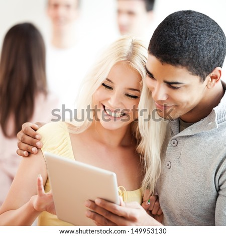 Man and woman watching something on a digital tablet. - stock photo
