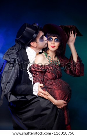 man and woman  wearing  as  vampire and  pregnant witch. Halloween. , Joke - stock photo