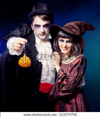 Man and woman wearing as vampire and witch. Carnival. fog. - stock photo