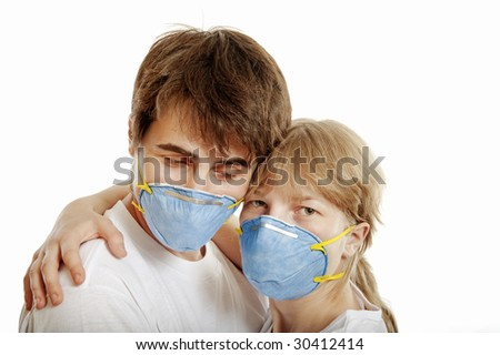 Man and woman wearing  respirators hug one another against white background - stock photo