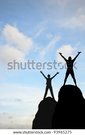 man and woman were placed on top of the hill hand in hand against the sunny sky - stock photo