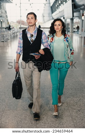 Man and woman with a briefcase arriving at the airport.  - stock photo