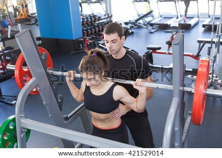 man and woman with barbell flexing muscles in gym. woman and personal trainer in gym - stock photo