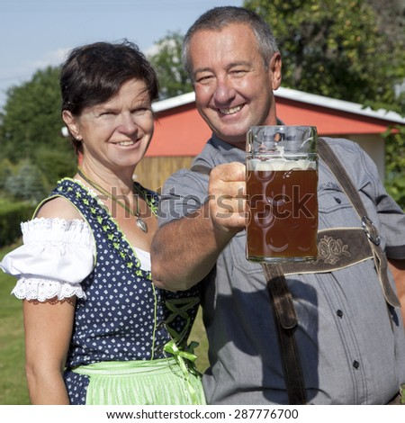 Man and woman with beer mug in Bavaria - stock photo