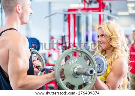 Man and woman with dumbbells in gym exercising together pretty motivated - stock photo