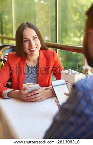 man and woman with smartphones sitting on cafe. smiley woman looking at man - stock photo