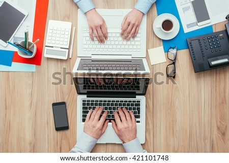Man and woman working at office desk with customized different workspaces, the woman's side is full and the man's side is clean and simple - stock photo