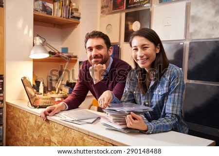 Man and woman working behind the counter at a record shop - stock photo