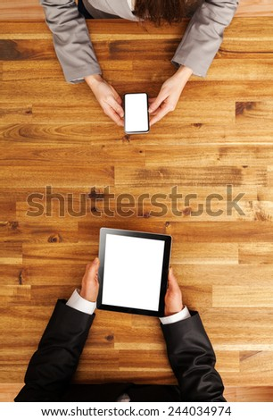 Man and woman working on mobile devices. Shot from above view - stock photo
