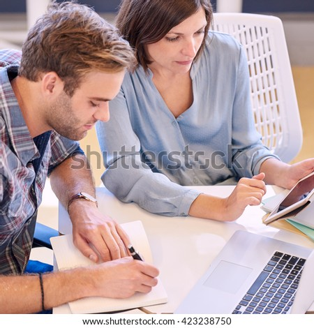 man and woman working together closely at work in office