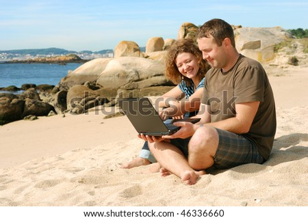 man and woman working with computer at beach