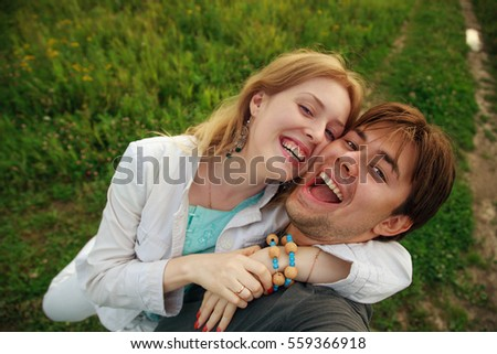 Man and woman young happy couple outdoors portrait. Man holding camera making selfie.