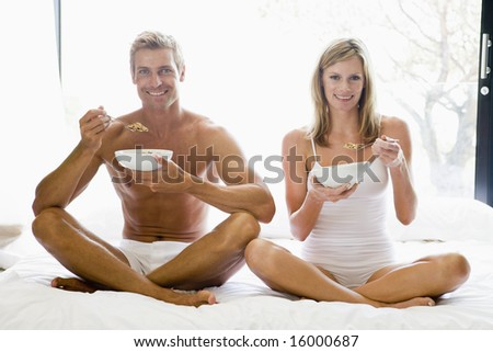 Man and women eating breakfast on a bed - stock photo