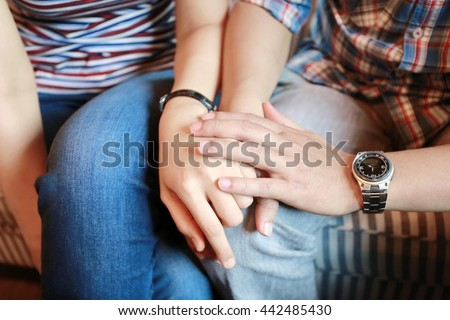 man and women holding hand together, family concept, warm feeling between man and woman sit together on sofa and hand hold for power up heart energy, serious and worry feeling - stock photo