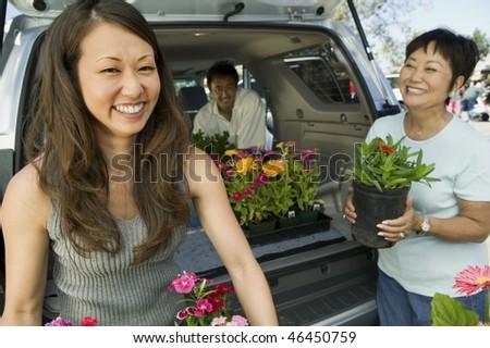 Man and Women Loading Plants - stock photo