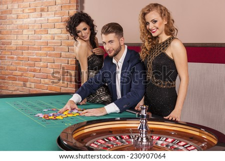 Man and women playing roulette at casino - stock photo