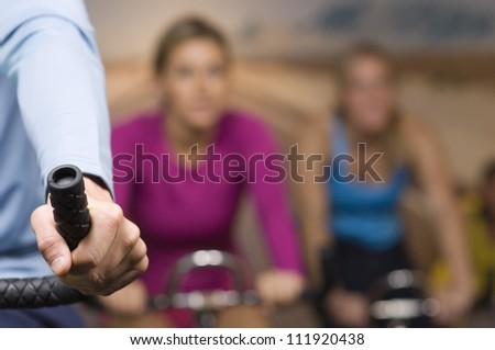 Man and women riding an exercise bike - stock photo