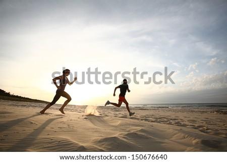 Man and women running on beach at sunset - stock photo
