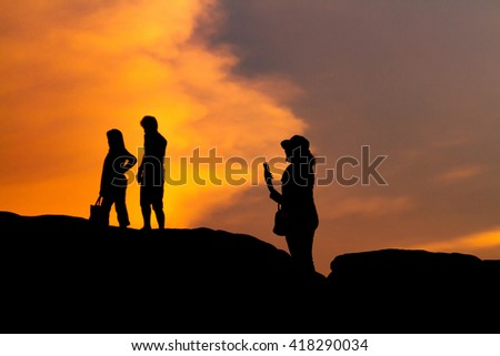 man and women silhouette photography and selfie with mountain at sunset .,soft focus