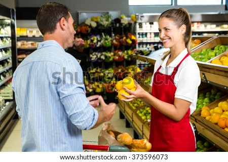 Man and worker discussing fruit in grocery store