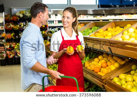 Man and worker discussing fruit in grocery store - stock photo
