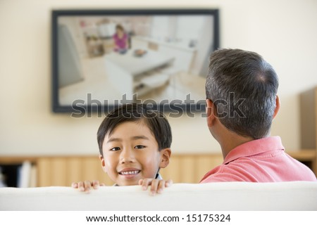 Man and young boy in living room with flat screen television smiling - stock photo