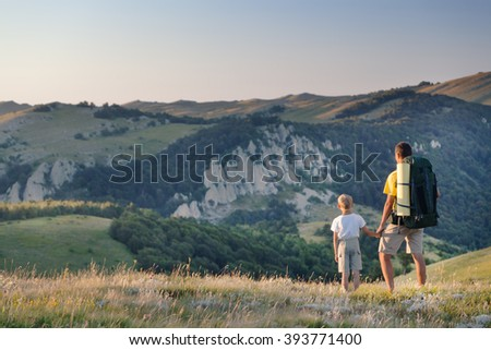 Man and young boy standing in a mountain meadow. The man points to a direction, showing something to the boy. Summer season, clear blue sky. Dimergy Massif, Crimea, Russia