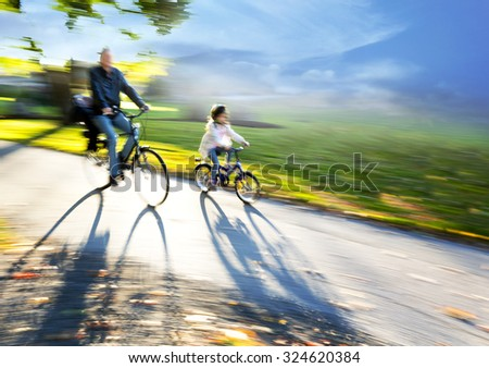 Man and young girl cycling together on sunny late afternoon in autumn