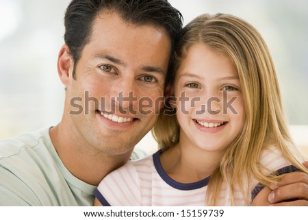 Man and young girl in living room smiling - stock photo
