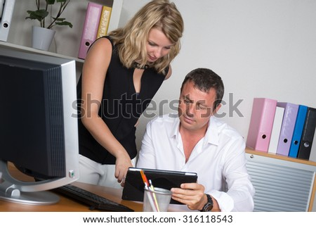 Man and young woman at office working together on tablet