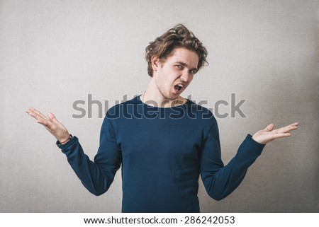 Man angry, shouts, lifting his hands up. Gray background
