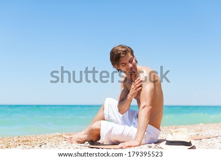 man apply sunscreen protection lotion on back tanned body, sitting on summer beach travel ocean vacation, concept of applying skin care sun protect
