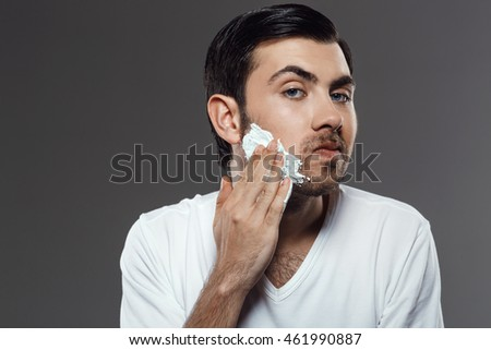 Man applying cream for shave on face over grey background.