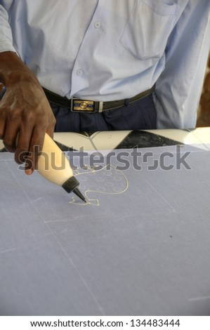Man applying paint on fabrics in Zambia, Africa