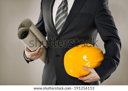 man architect wearing suit holding blueprint and helmet confident construction manager with architectural project papers