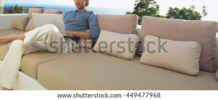 man are sitting relaxed on cozy couch on open terrace with laptop - stock photo