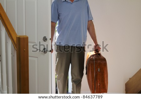 Man arriving from business travel inside the front door of his home.